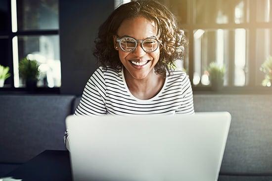 Kuvituskuva. Silmälasipäinen nainen kirjoittaa hymyillen kannettavalla tietokoneella.