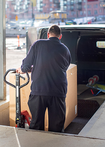 Mies lastaa suurta pahvilaatikkoa pakettiautoon.