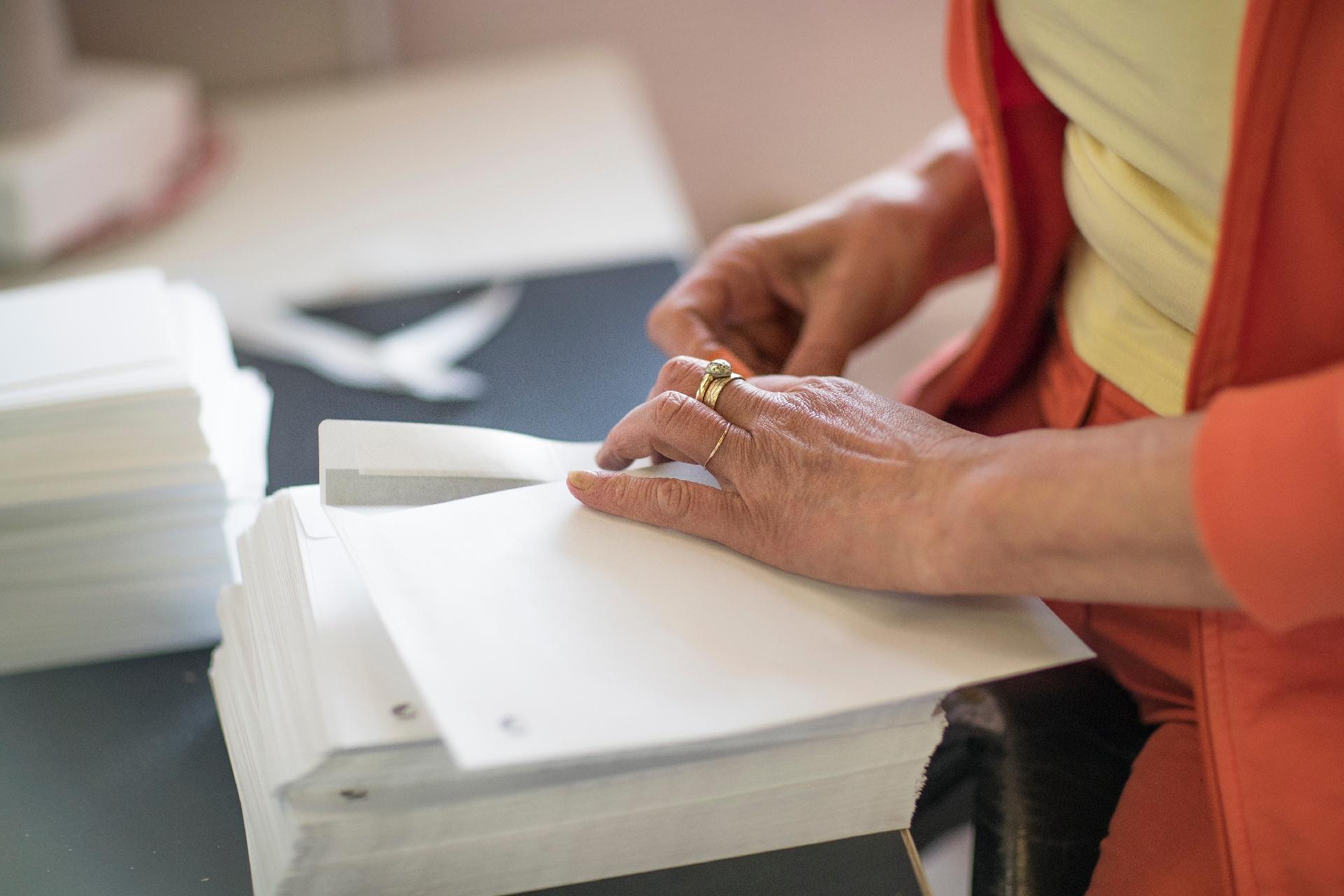 Valmennettava käsittelee papereita printti- ja postituspalveluiden työelämäympäristössä.