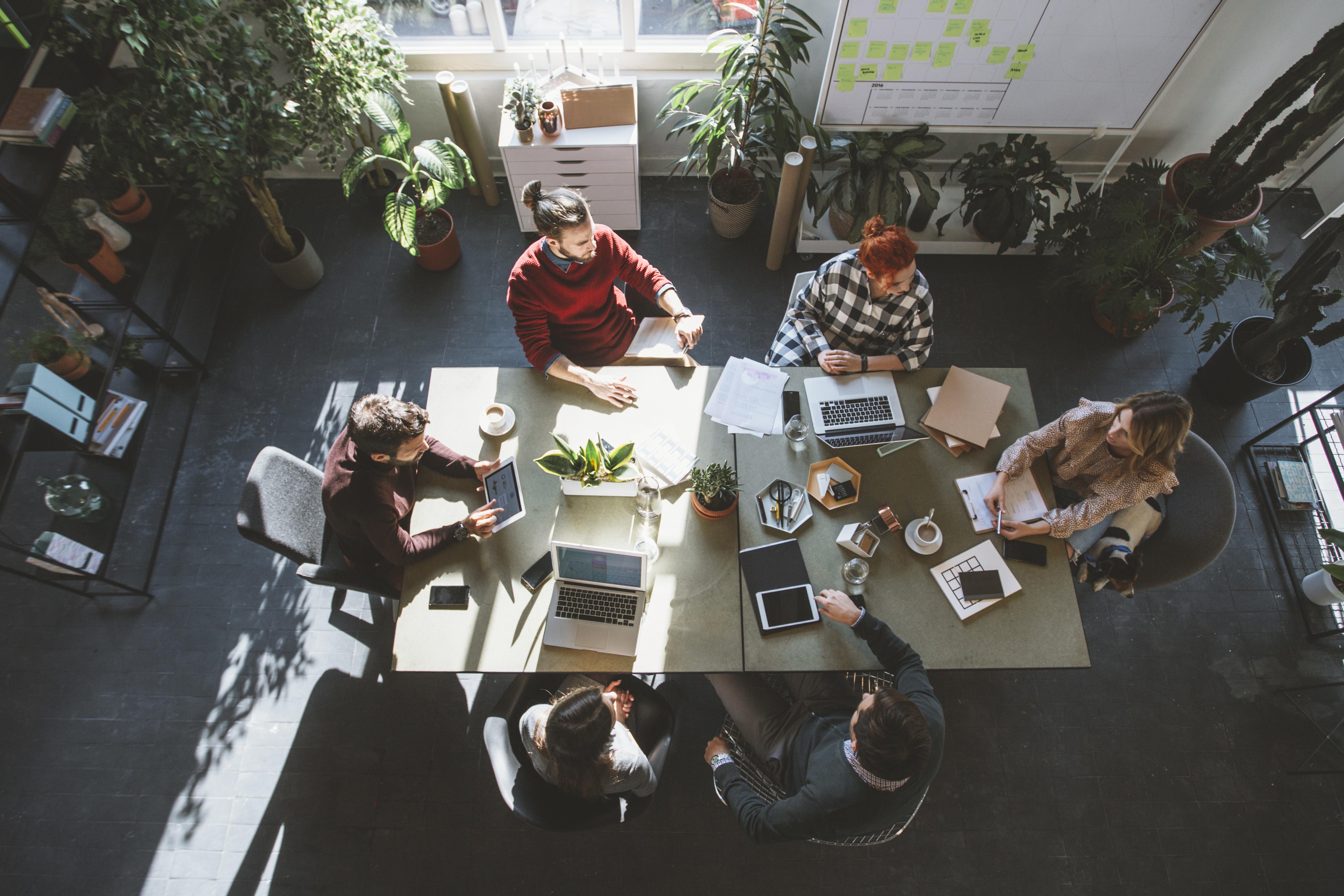 Työpöydän äärelle istuvat työntekijät.