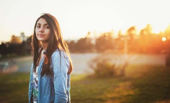 Kuvituskuva. Nuori seisoo niityllä ilta-auringossa ja hymyilee kameralle.