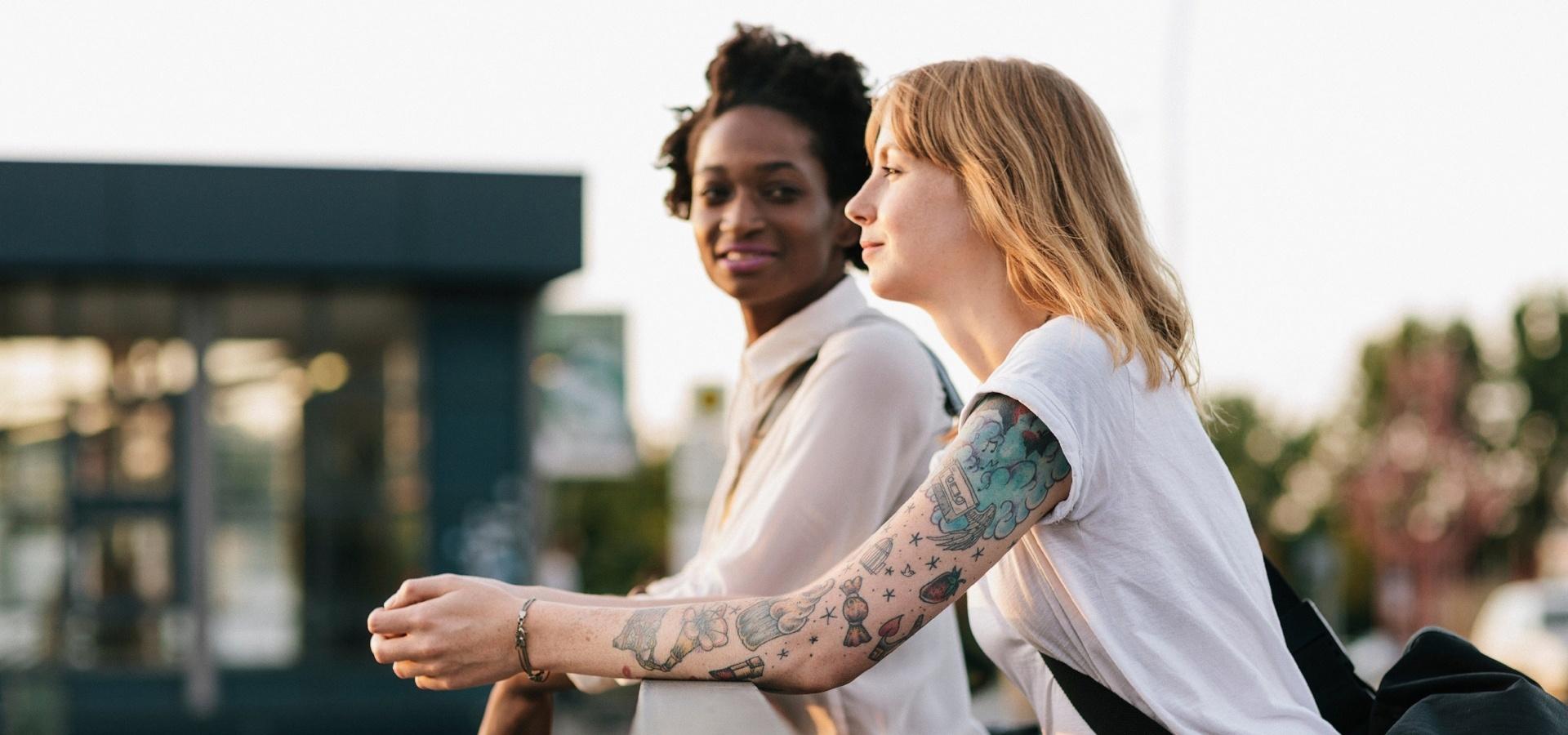 Kuvituskuva. Kaksi nuorta nojaa hymyillen ulkona kaiteeseen.