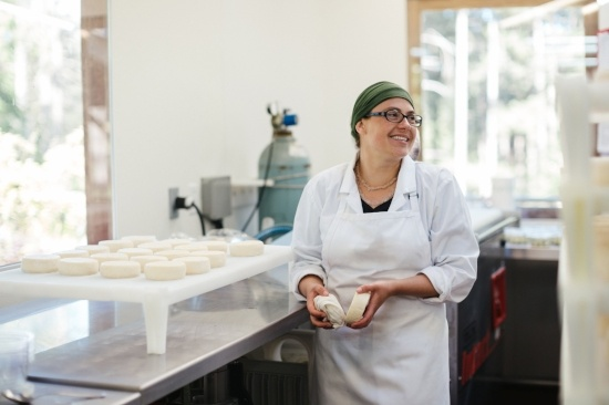 Kuvituskuva. Nainen seisoo keittiössä, hymyilee ja pitää kädessään taikinanpalaa..