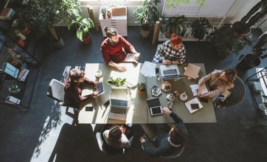 Kuvituskuva. Ihmiset ovat kokoontuneet pöydän ääreen kokoustamaan.