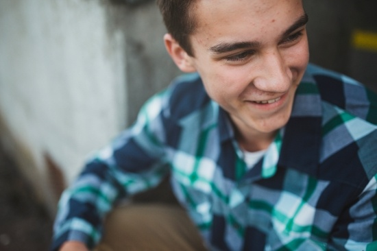 Ruutupaitainen poika lähikuvassa hymyilee.