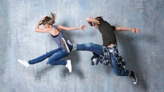 Kuvituskuva. Kaksi ihmistä hyppää ilmaan.