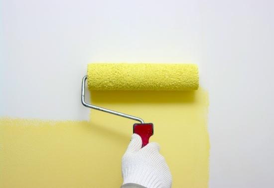 Kuvituskuva. Lähikuva kädestä, joka maalaa seinää maalirullalla keltaiseksi.