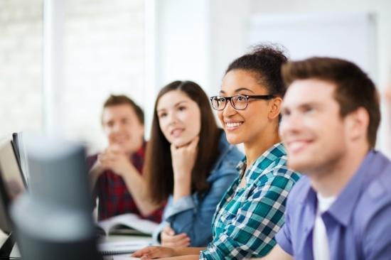 Kuvituskuva. Neljä ihmistä istuu tietokoneiden ääressä ja kuuntelee opettajaa.