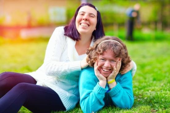 Kuvituskuva. Kaksi naista hymyilee, toinen makaa nurmikolla ja toinen istuu hänen vieressään.