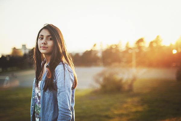 Tyttö pellolla jonne lankeaa auringonlasku