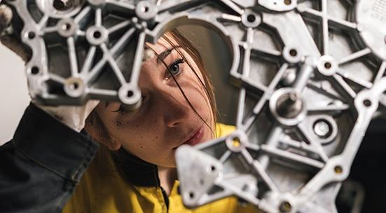 Kuvituskuva. Tyttö korjaamassa laitetta.